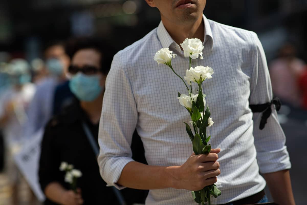 Mustan surunauhan käteensä solminut mies kantaa valkoisia kukkia perjantaina kuolleen opiskelijan muistoksi järjestetyssä mielenosoituksessa Hongkongissa.