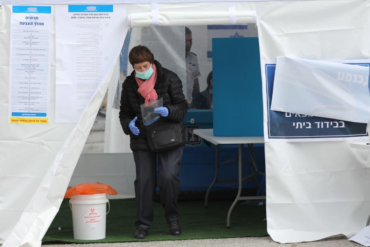 Nainen kävi äänestämässä koronaviruksen vuoksi eristyksiin pantujen erityisellä äänestyspisteellä parlamenttivaaleissa Israelissa