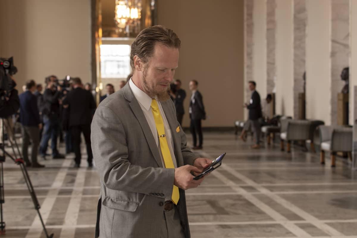 kansanedustaja juho eerola käyttää kännykkää eduskunnan valtiosalissa