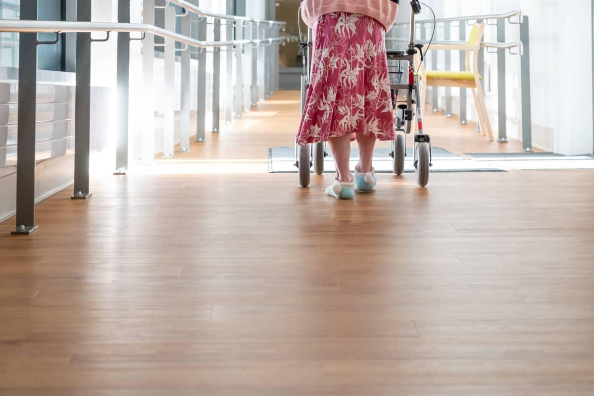 Vanhus kävelee rollaattorin kanssa kaltevaa käytävää Myyrmäen vanhustenkeskuksessa, Vantaalla.