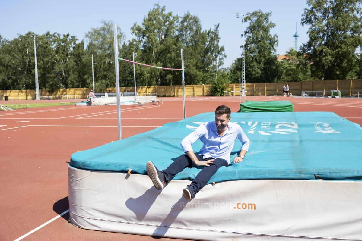 Mies istuu turkoosilla korkeushypyn laskeutumispatjalla ja nauraa. Taustalla näkyy urheilukenttää.