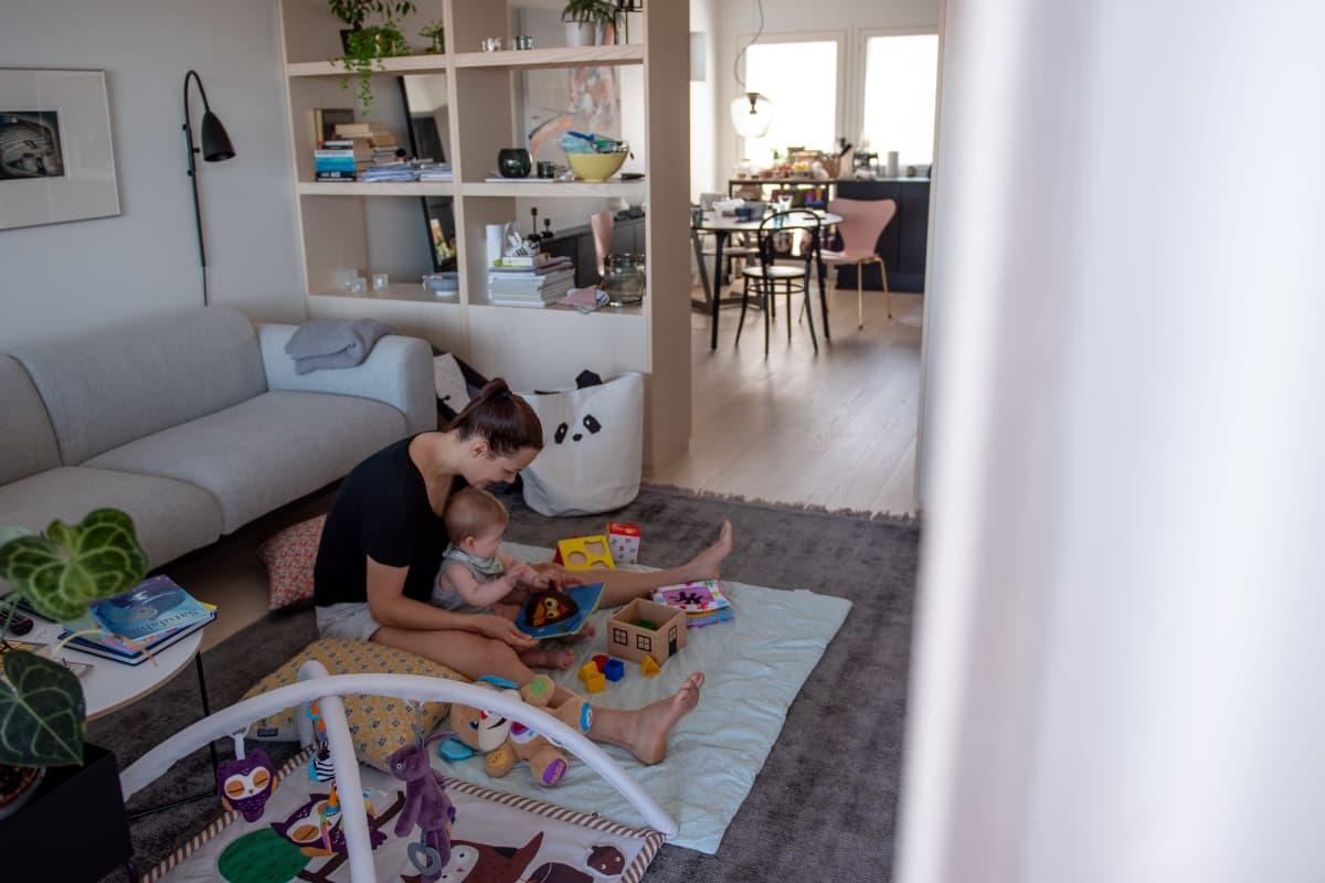 Outi Ellilä leikkii lapsensa kanssa lattialla.