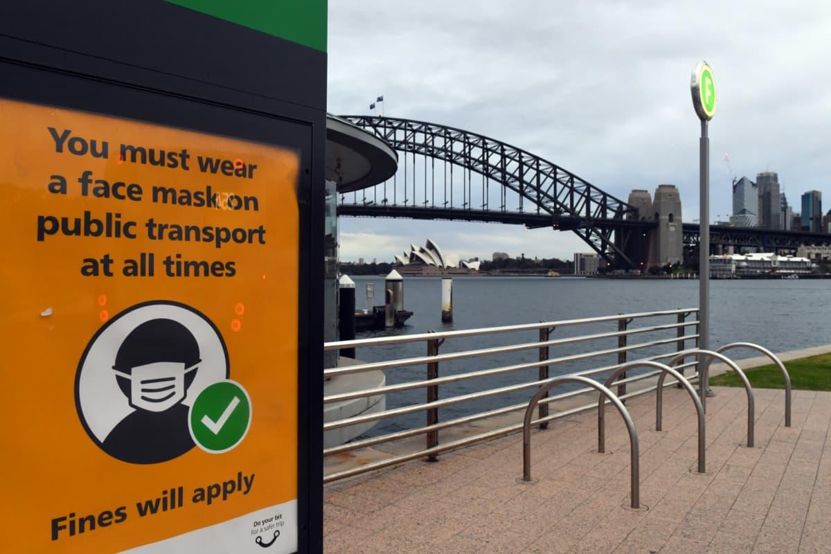 Kyltissä lukee: Julkisessa liikenteessä on aina käytettävä kasvomaskia sakon uhalla, taustalla Sydneyn keskustaa