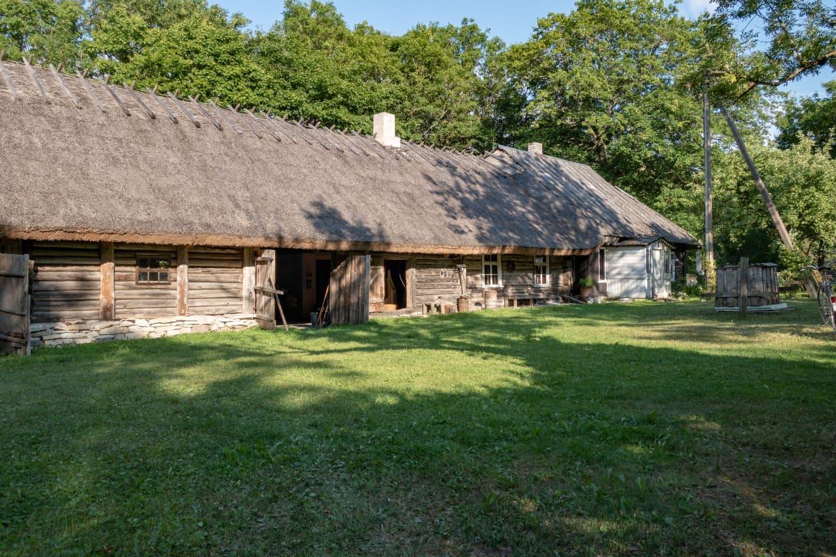 Vanha saarenmaalainen pitkä olkikattoinen perinnetalo Virossa.
