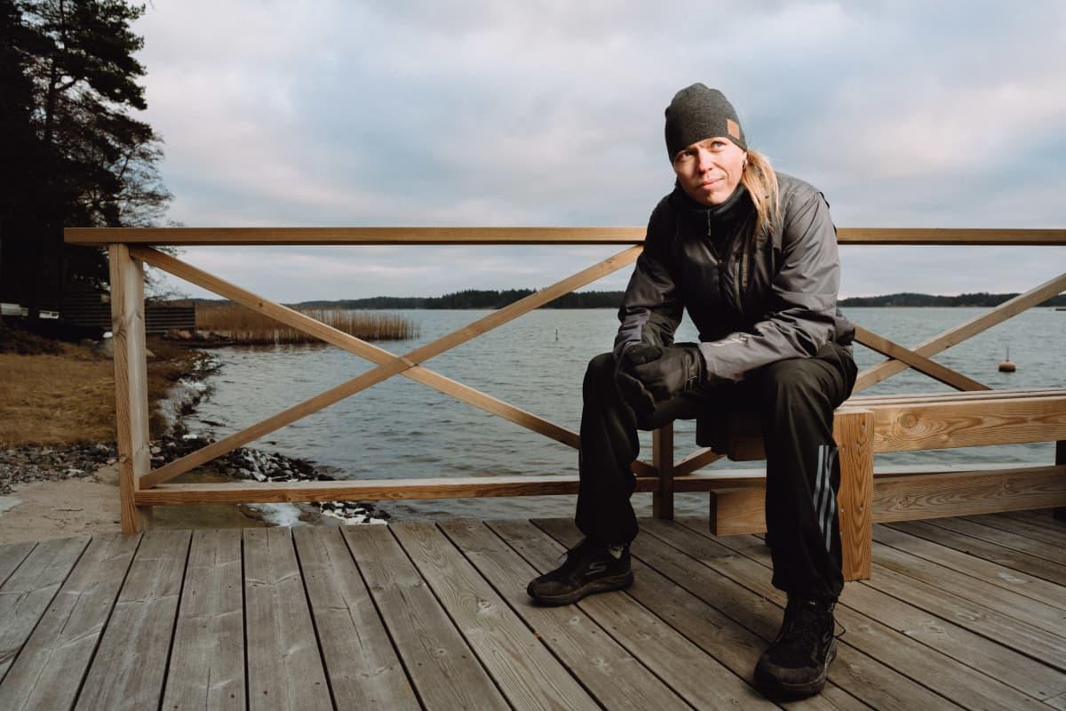 Kuvassa sellisti Eicca Toppinen istuu laiturilla rannassa ja katsoo merelle.