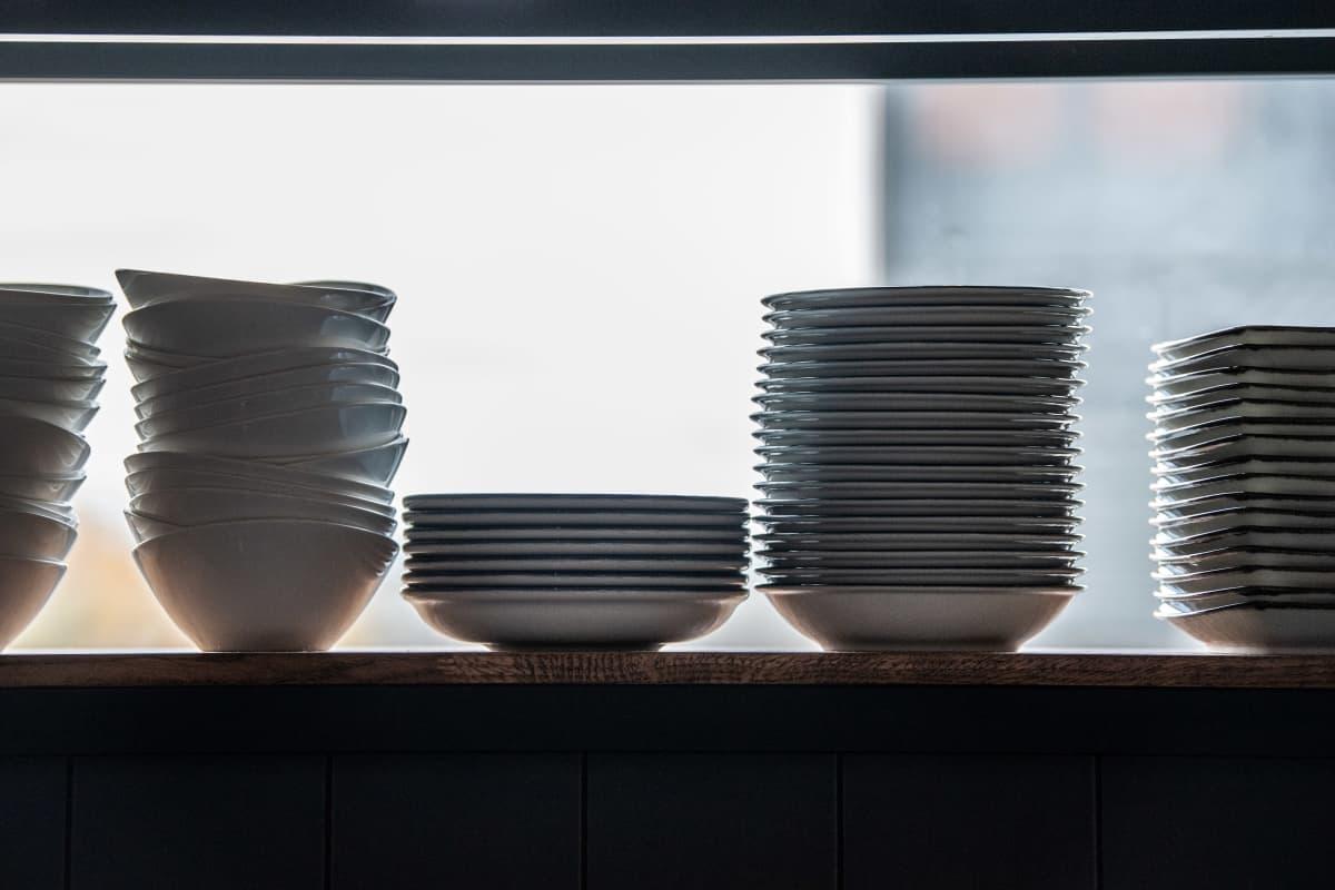 Erilaisia lautasia pinottuna ravintolan hyllyssä.