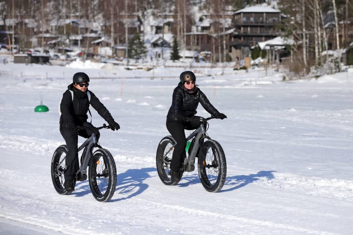 Kaksi talvipyöräilijää järven jäällä. Taustalla hotelli Järvisydän.