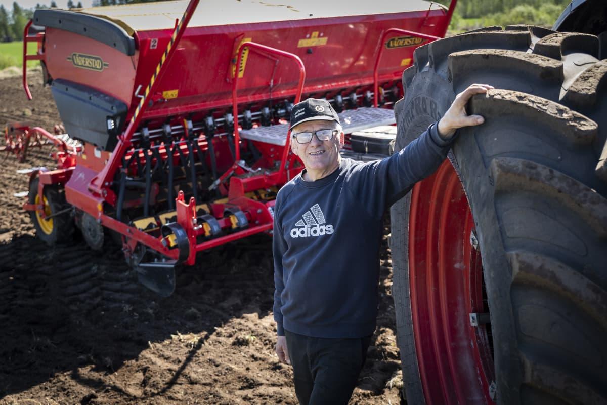 Eero Polso nojaa traktorin renkaaseen. Taustalla on traktorin perässä vedettävä kylvökone.