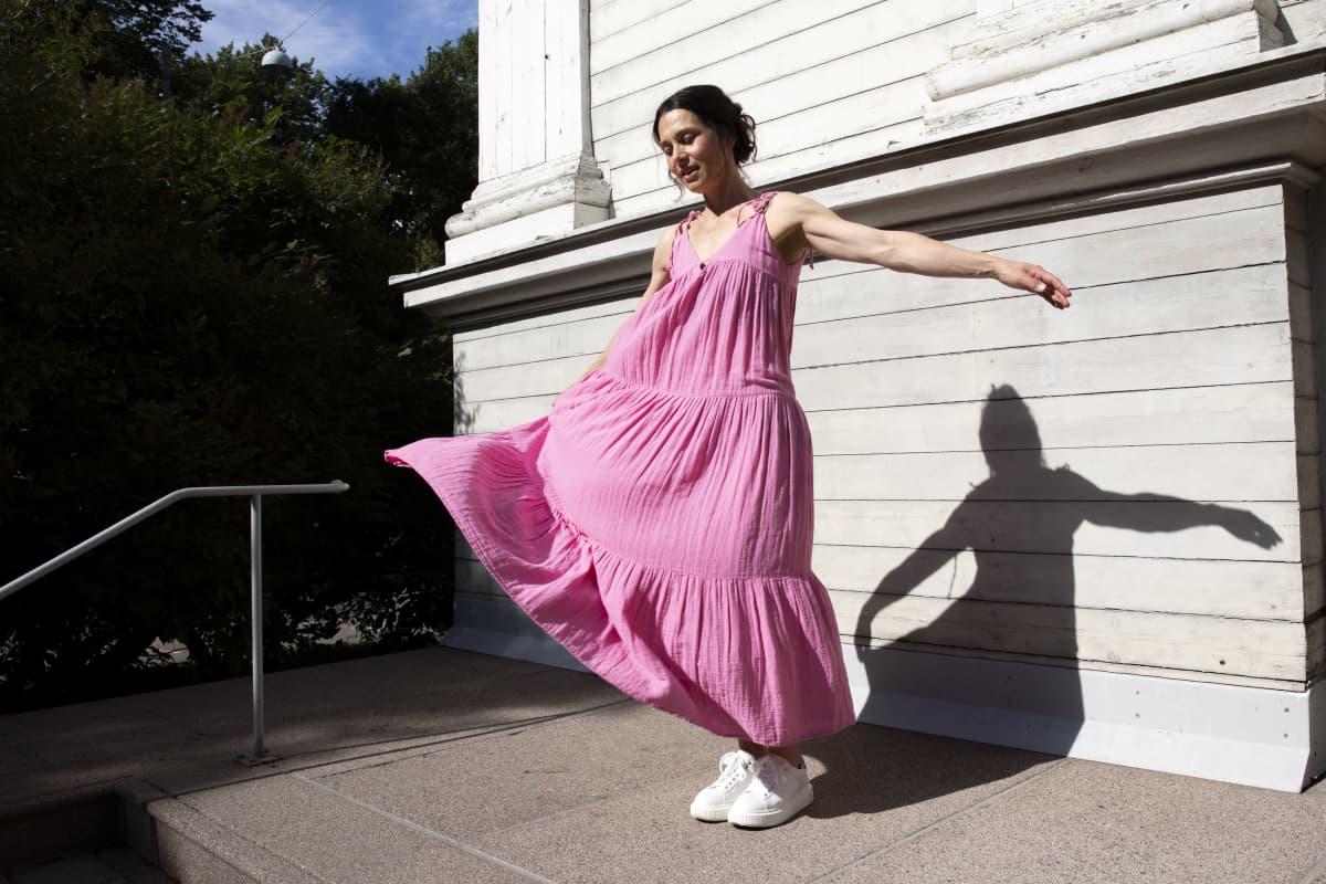 Nainen vaaleanpunaisessa kesämekossa levittää käsiä tanssiin. Nainen on ulkona, takana valkoinen lautaseinä. Naisen varjo piirtyy seinään.