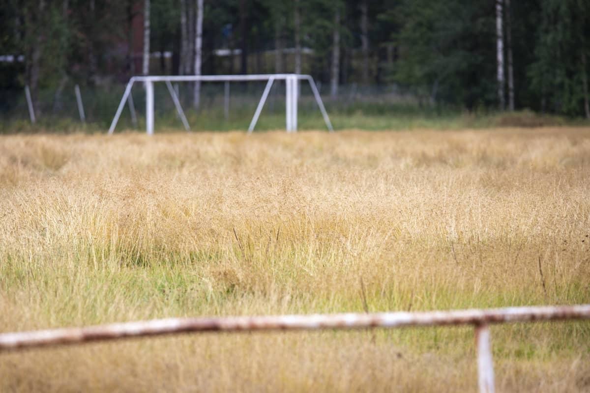 Voikkaan pallokentällä kasvaa heinää, taustalla jalkapallomaalit ilman verkkoa