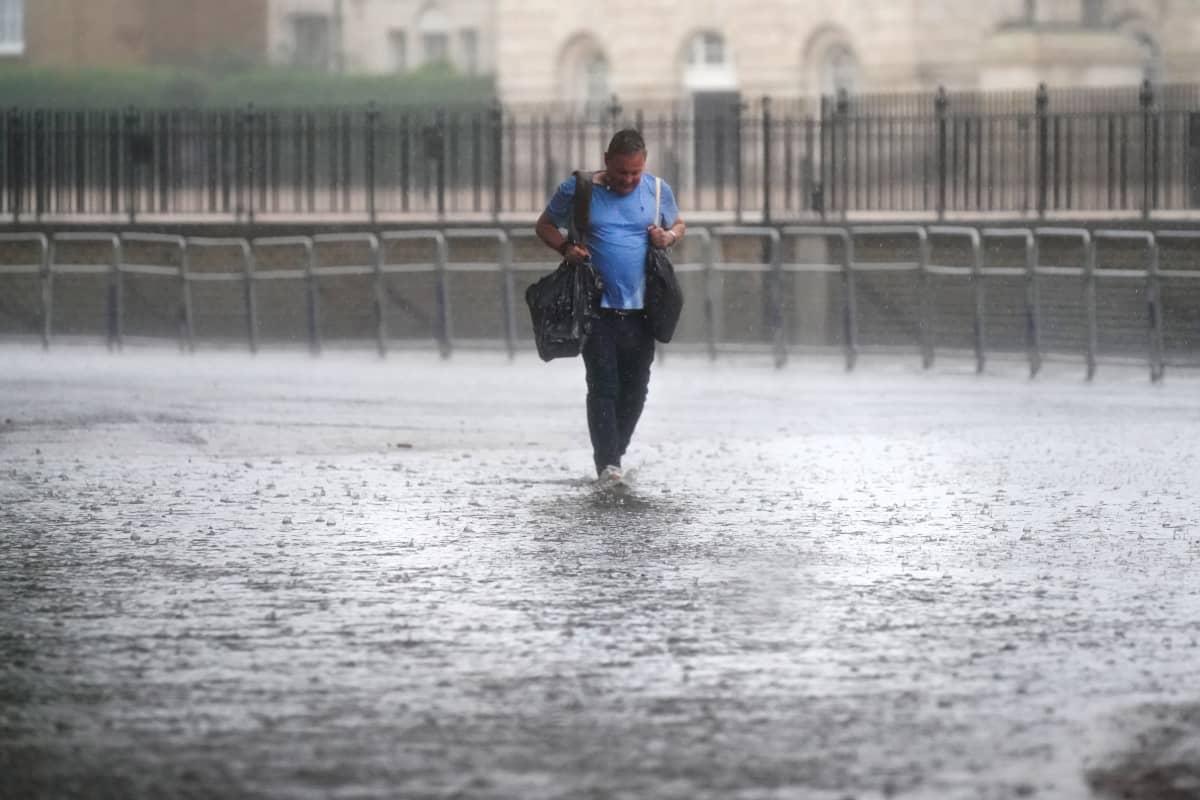 Mies kävelee tulvivalla tiellä.