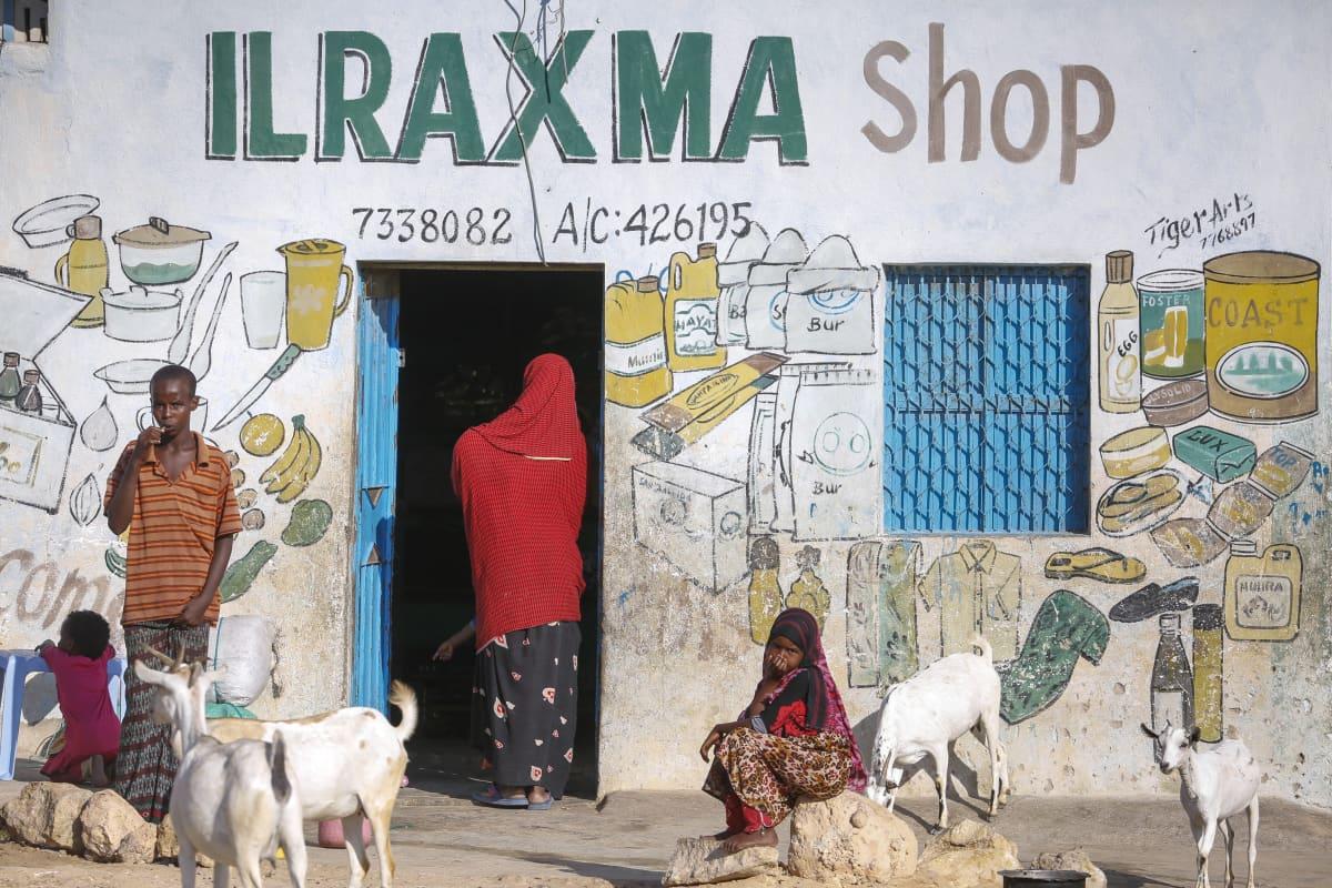 Nainen, poika ja tyttö sekä vuohet kaupan edessä.