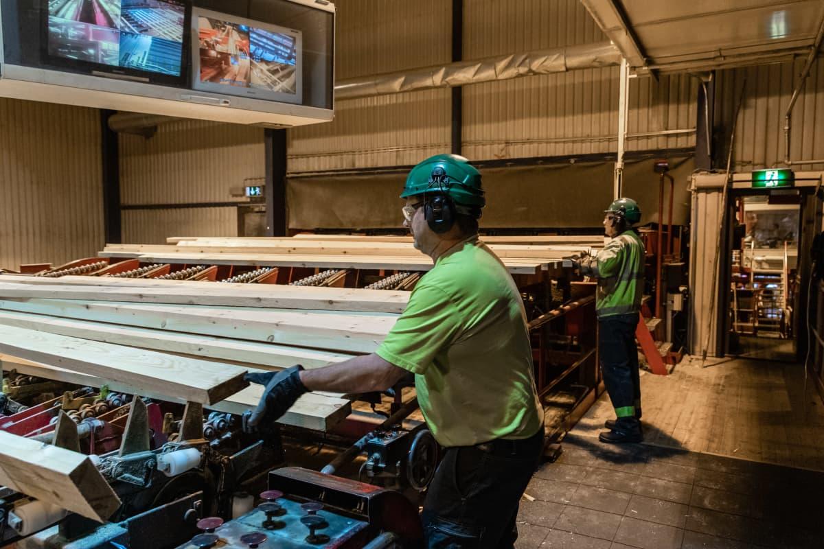UPM Kaukaan sahan työntekijöitä kääntelemässä lautoja linjastolle.