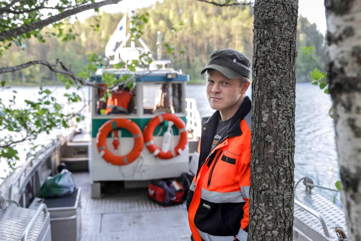Leo Parkkonen nojaa puuta vasten. Taustalla Metsähallituksen vene.
