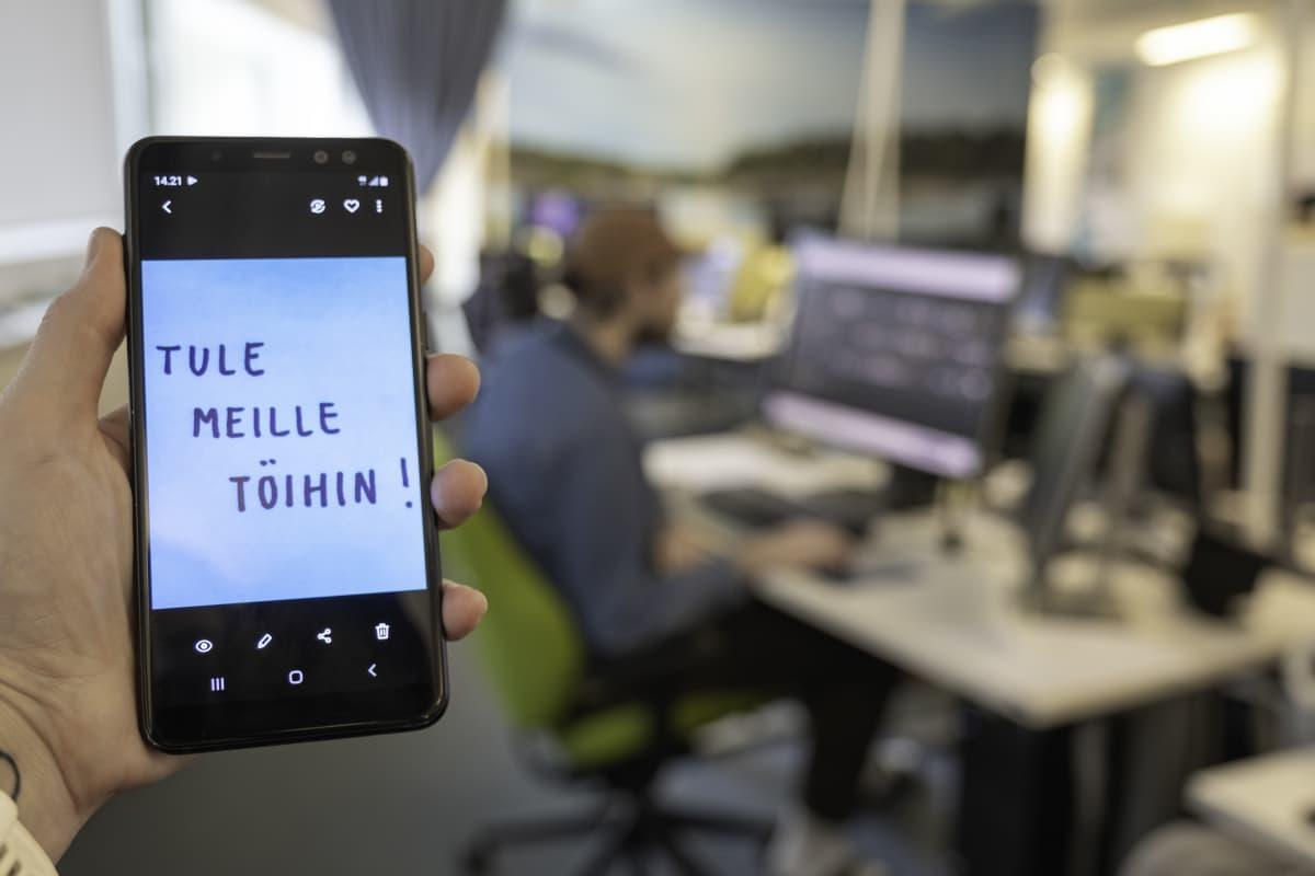 """""""Tule meille töihin"""" teksti kännykän näytössä, taustalla graafikko työssään."""