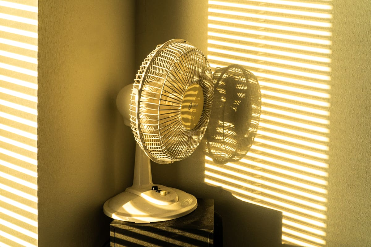 Sähkökäyttöinen tuuletin huoneen nurkassa helteellä.