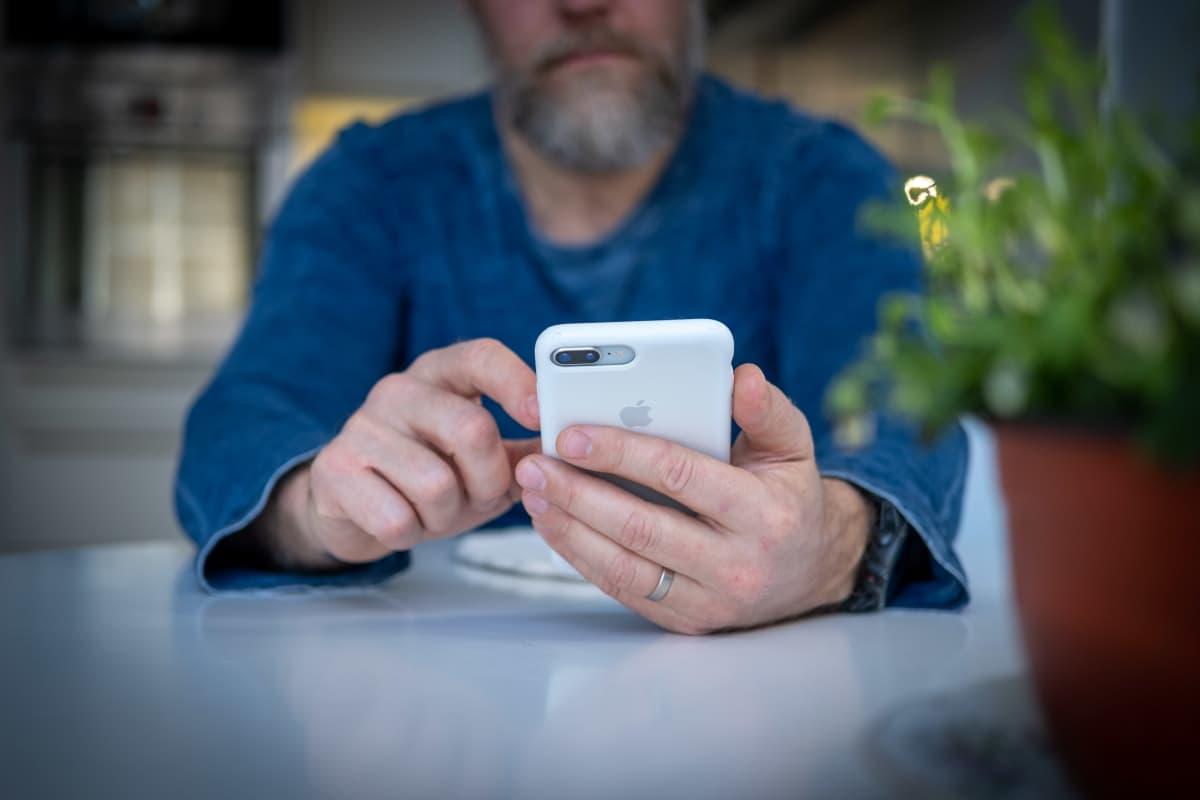 Lähikuvassa mies käyttää matkapuhelinta.