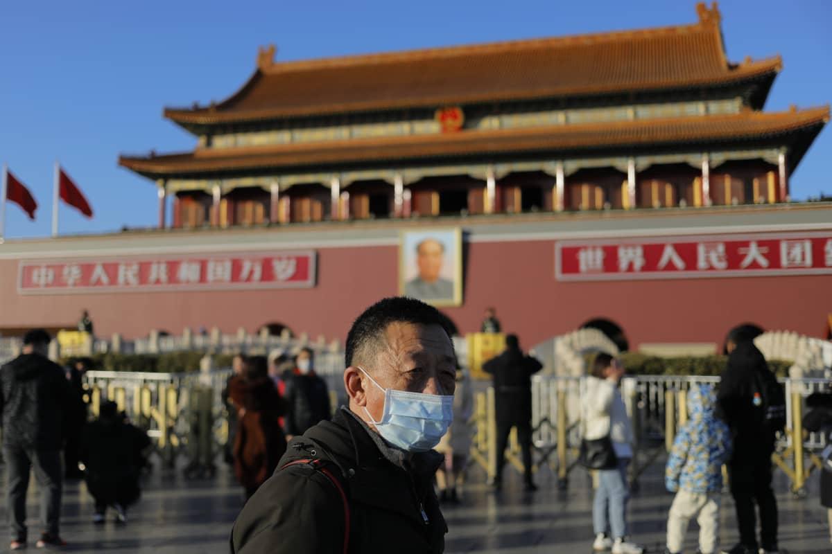 Kiinan pääkaupungissa Pekingissä turistit vierailevat Taivaallisen rauhan aukiolla tavalliseen tapaan. Mies puki ylleen hengityssuojaimen. Maassa on vahvistettu reilut 200 uutta koronavirustartuntaa, kolme ihmistä on kuollut tautiin.