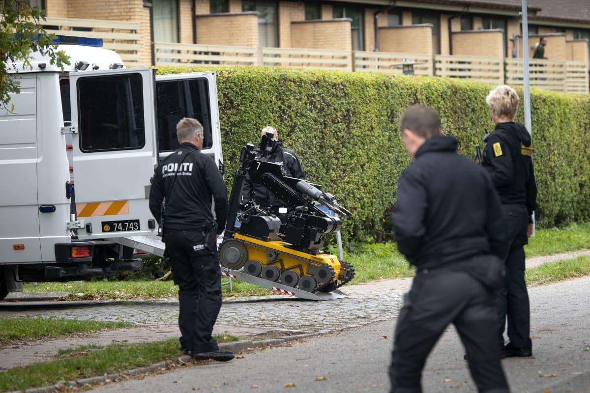 Poliisit seuraavat pommirobotin siirtämistä autosta.
