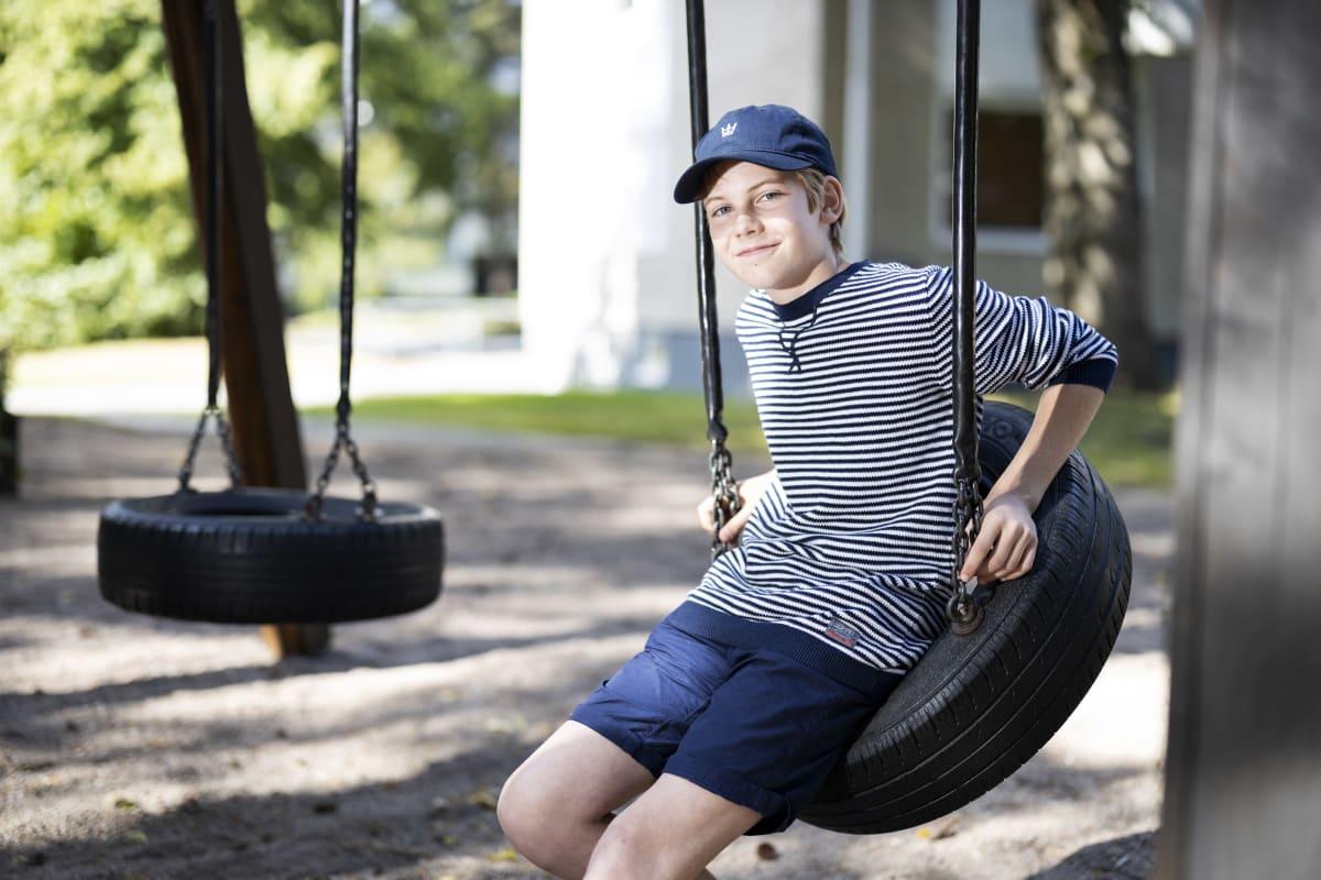 Poika istuu rengaskeinussa aurinkoisena päivänä sininen lippis päässään ja hymyilee.