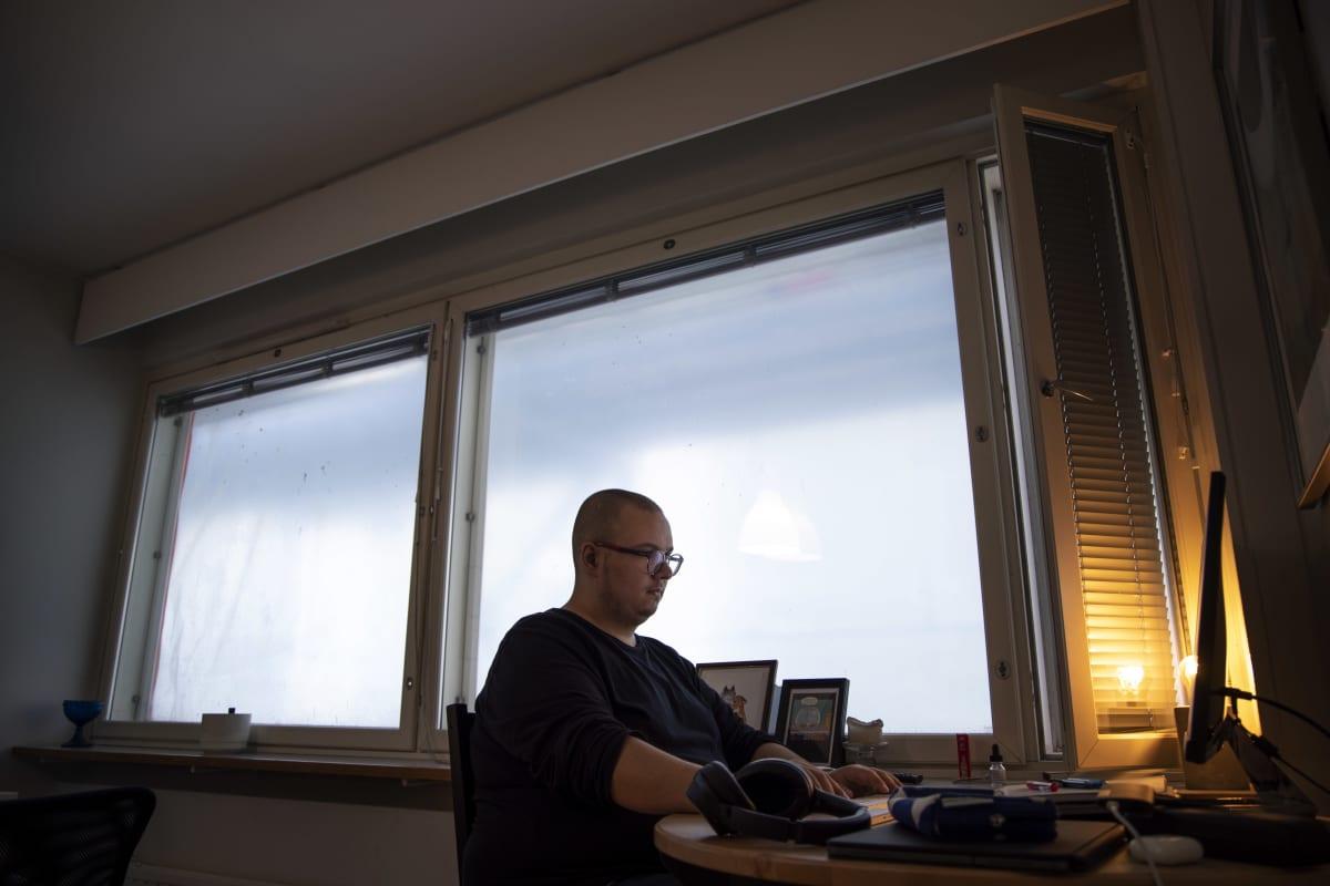 Benjamin Molini kotonaan Haagassa tietokoneen ääressä. Asunnon ikkunoista ei näy ulos eikä niitä saa auki, sillä talossa on käynnissä suuri julkisivuremontti.