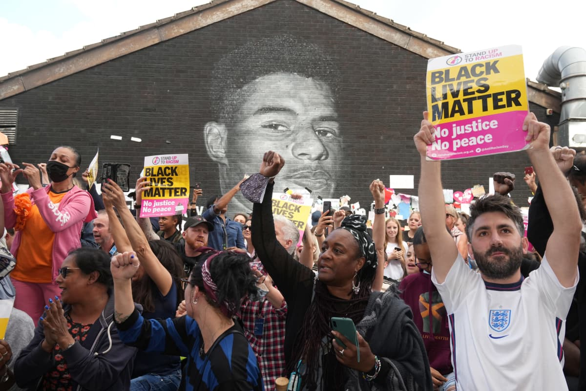 Ihmiset osoittamassa tukea Marcus Rashfordille muraalin edessä.