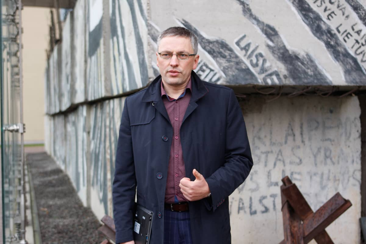 Mies seisoo betonisten barrikaadien edessä.