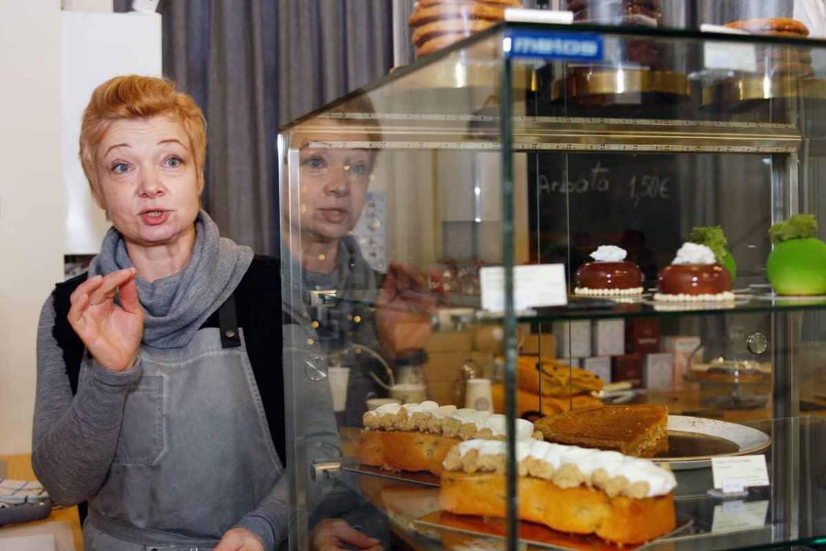 Nainen seisoo kahvilan tiskin takana.