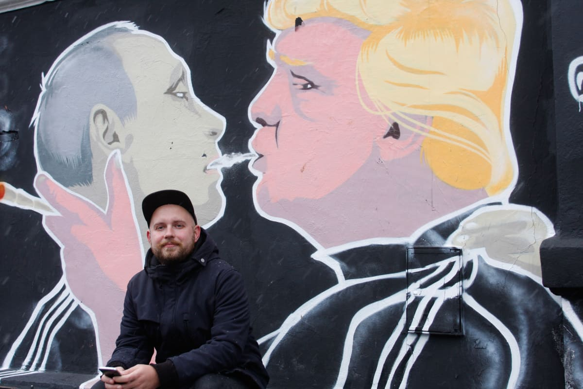 Mies istuu seinämaalauksen edessä. Siinä Putinin ja Trumpin kaltaiset hahmot kaulailevat.