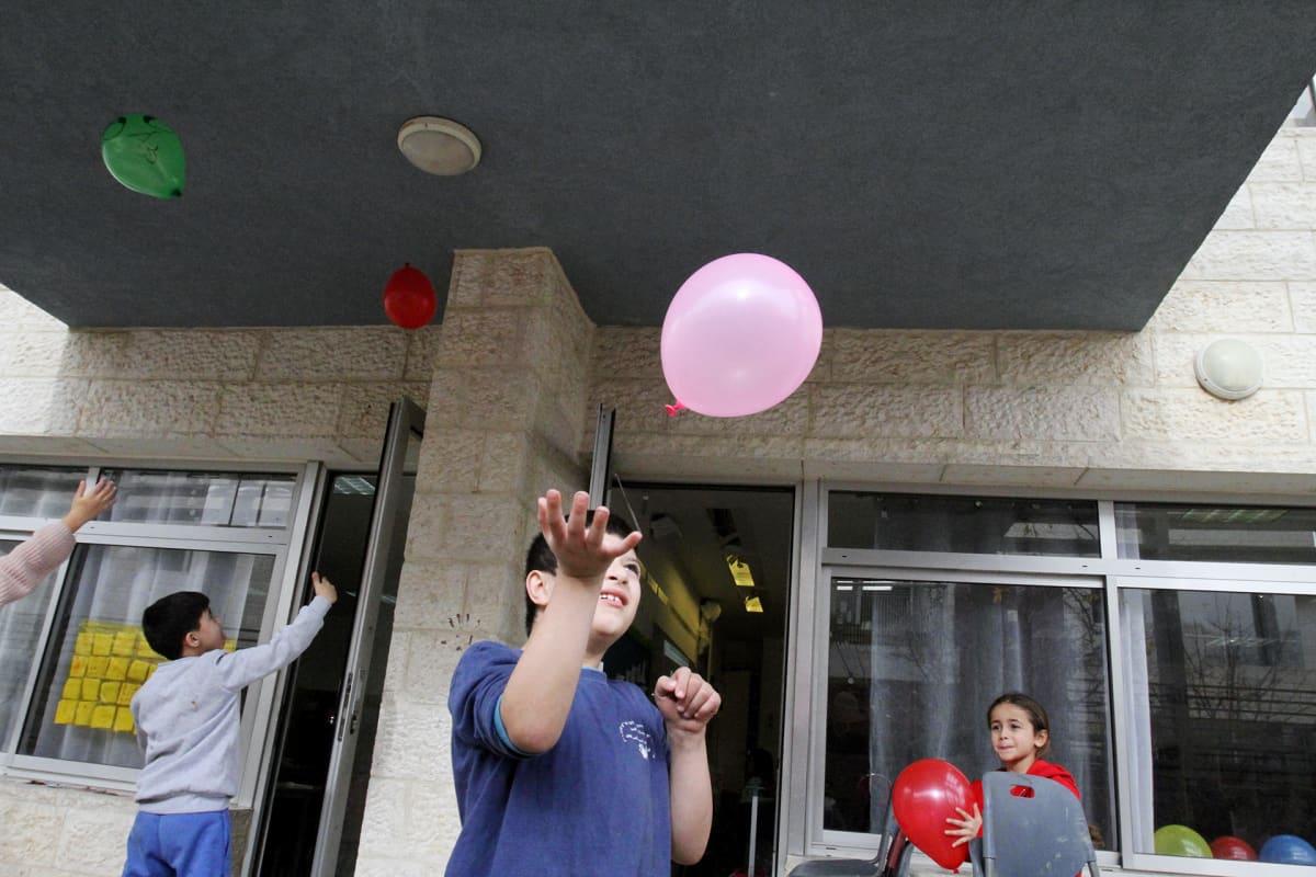 Lapset leikkivät ilmapalloilla yhteiskoulun pihalla Jerusalemissa.