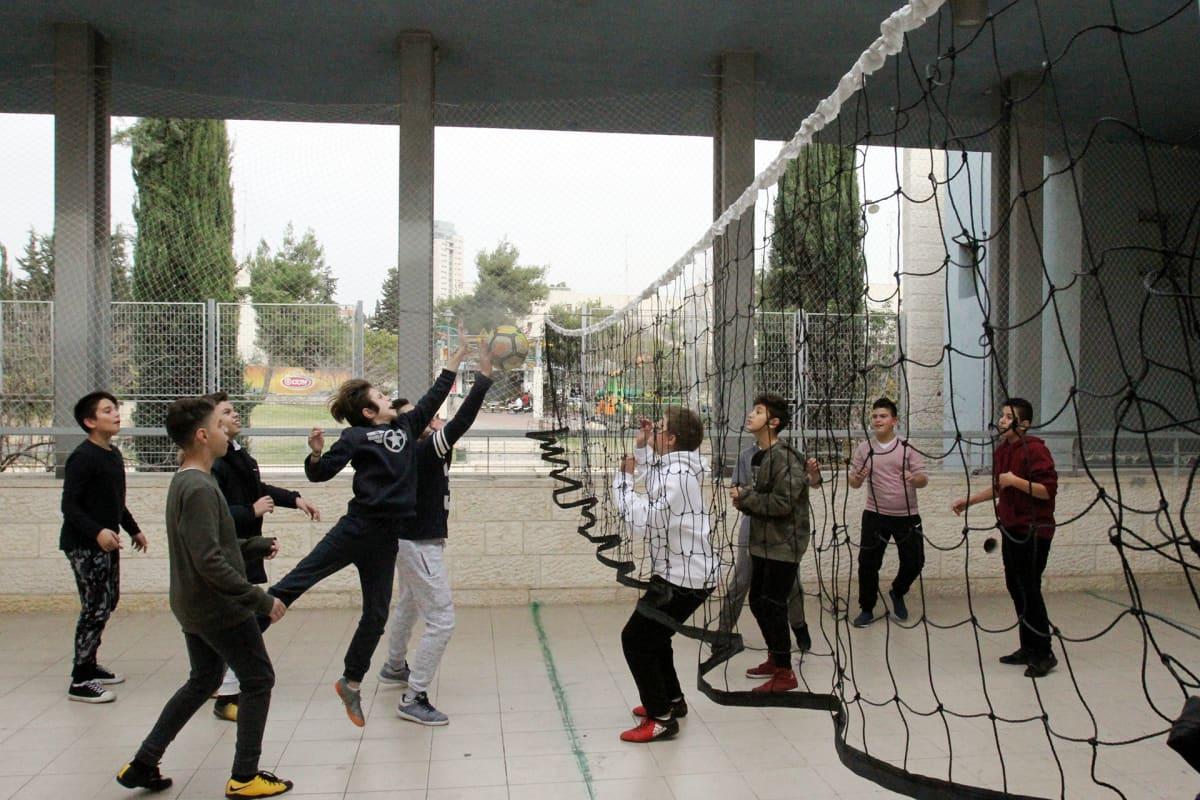Oppilaat pelaavat lentopalloa yhteiskoulun pihalla Jerusalemissa.