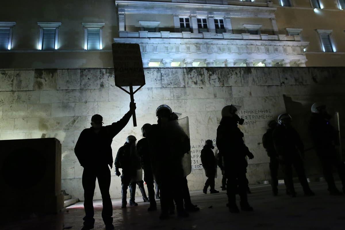 Mielenosoittajia valaistun parlamenttitalon edessä Ateenassa 15. tammikuuta 2018.
