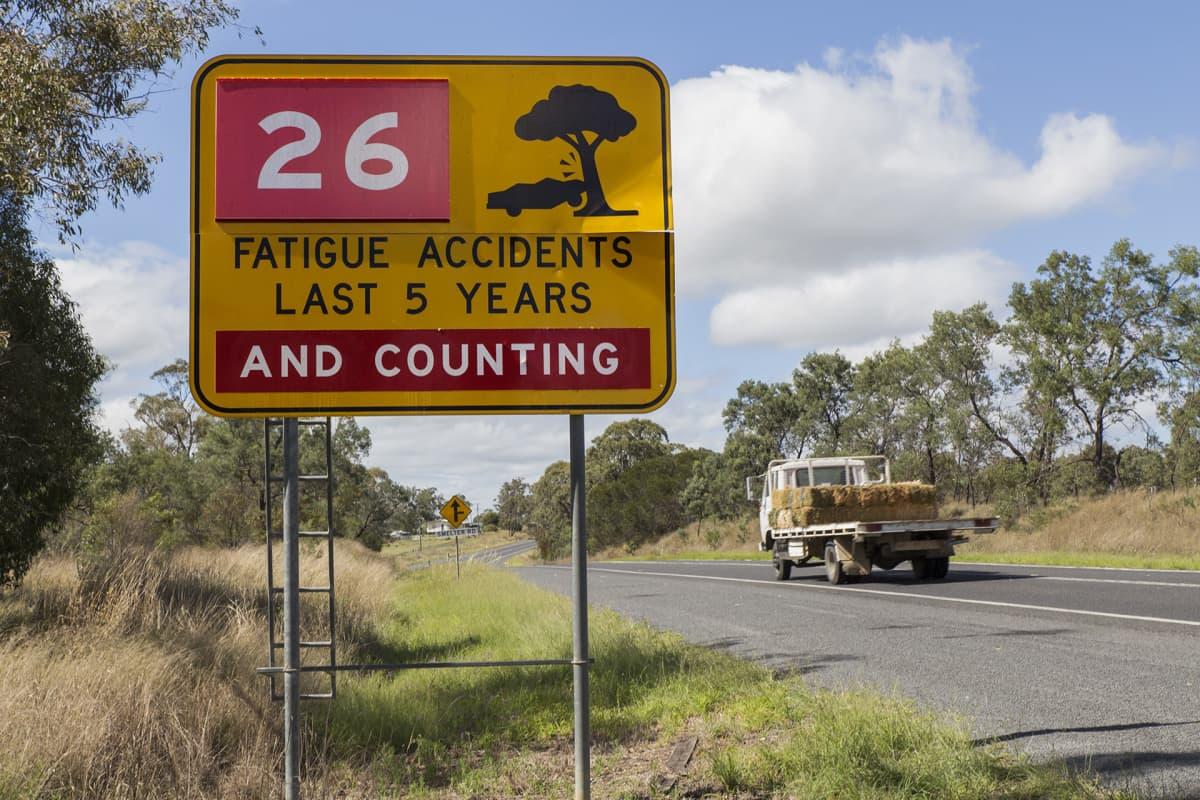 Liikennemerkissä on teksti, joka kertoo, että tiellä on ajettu 26 onnettomuutta, jotka ovat johtuneet väsymyksestä.