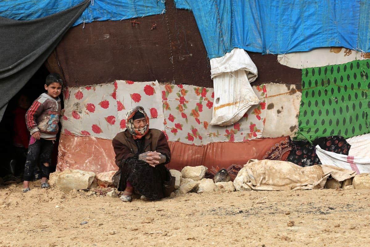 Nainen istuu teltan edessä. Poika seisoo vieressä.