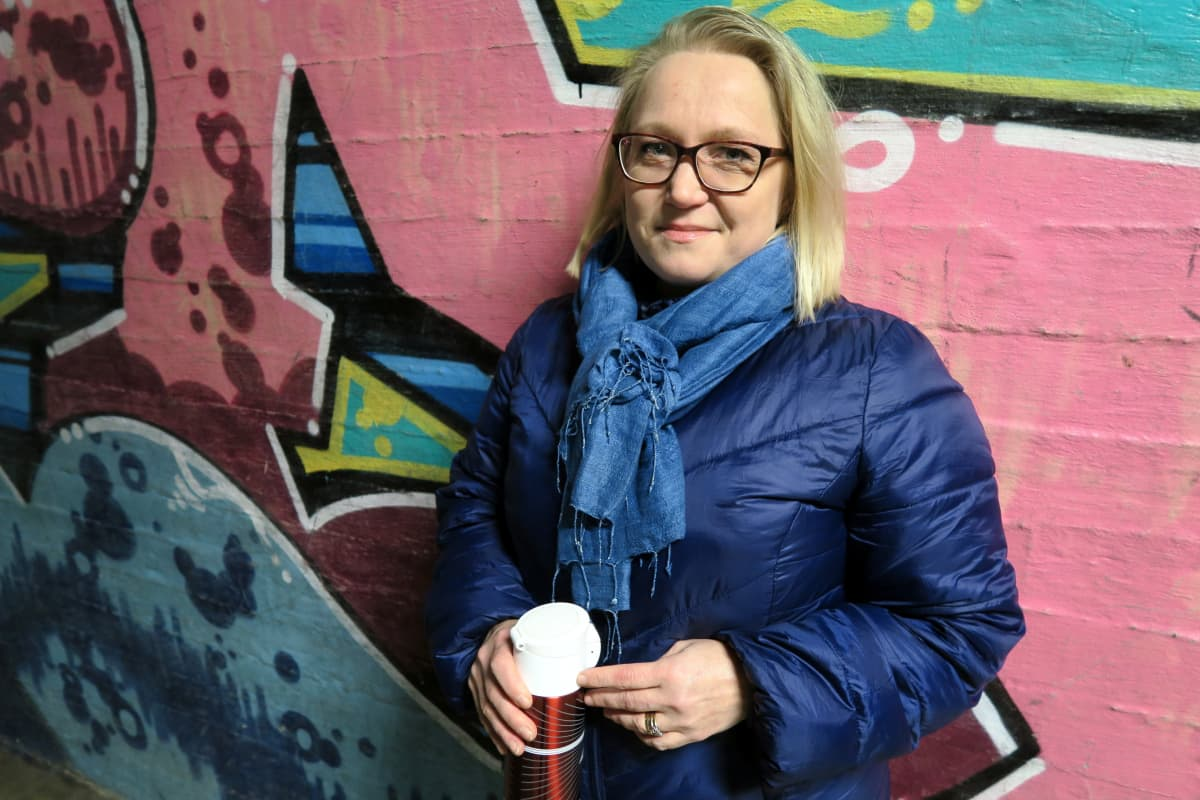 Vaaleahiuksinen nainen termari kädessä graffitiseinän edessä.