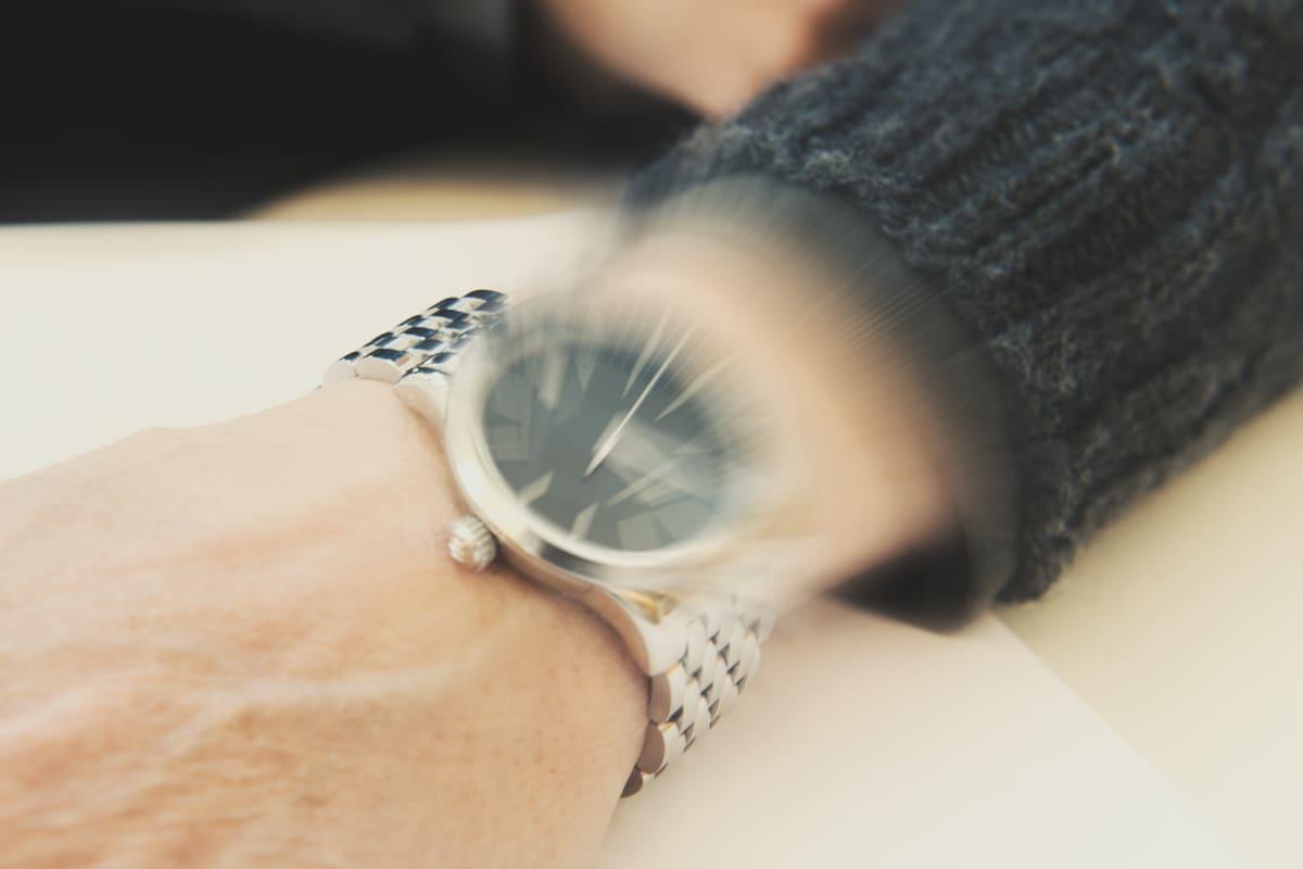 Epäterä rannekello miehen kädessä osoittamassa kiireistä aikataulua.