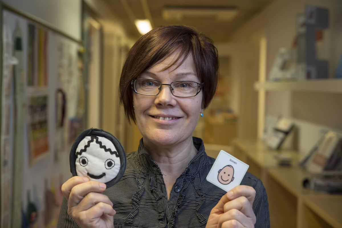 Tikoteekin kehittämispäällikkö Eija Roisko näyttää erilaisten naamojen kuvia.