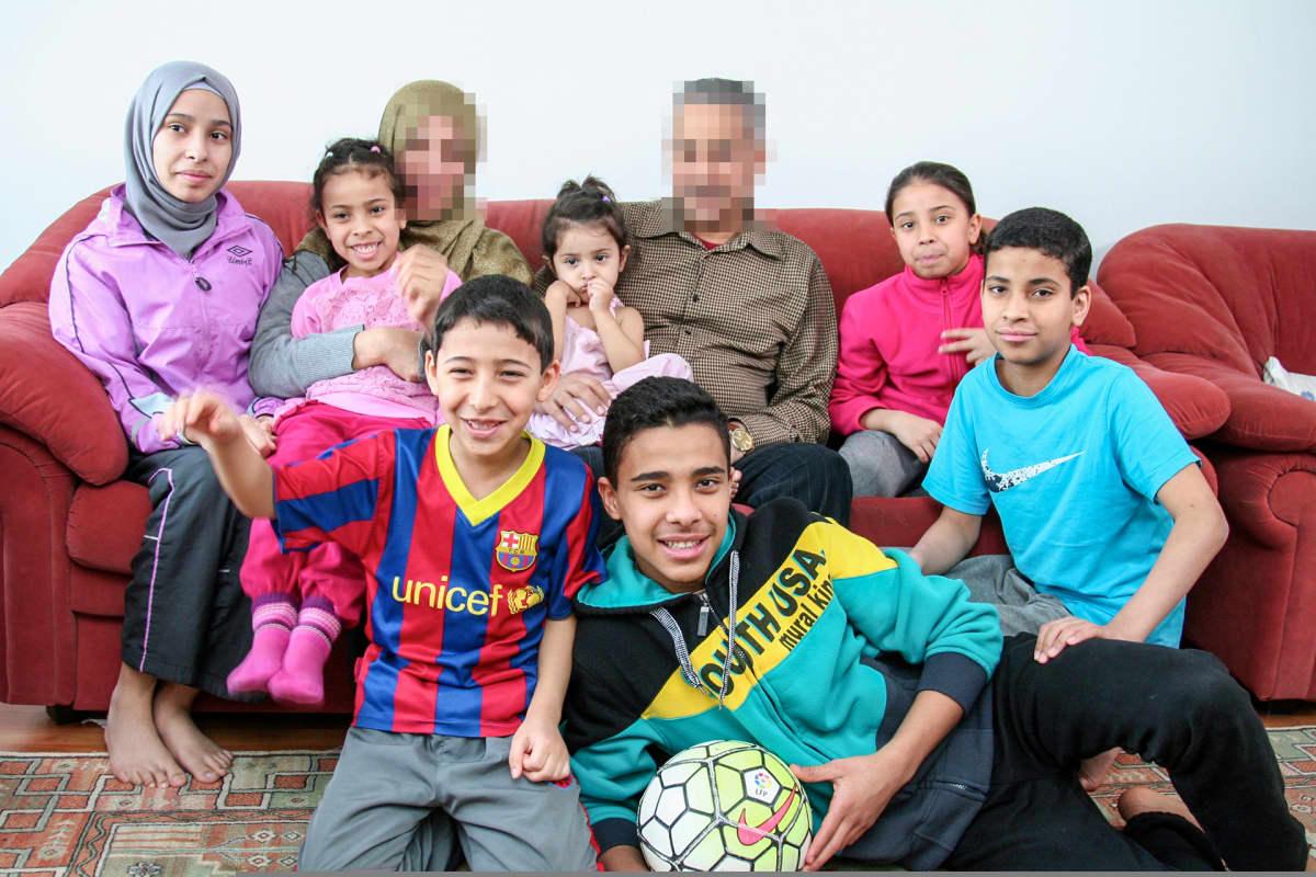 seitsenlapsinen perhe istuu sohvalla