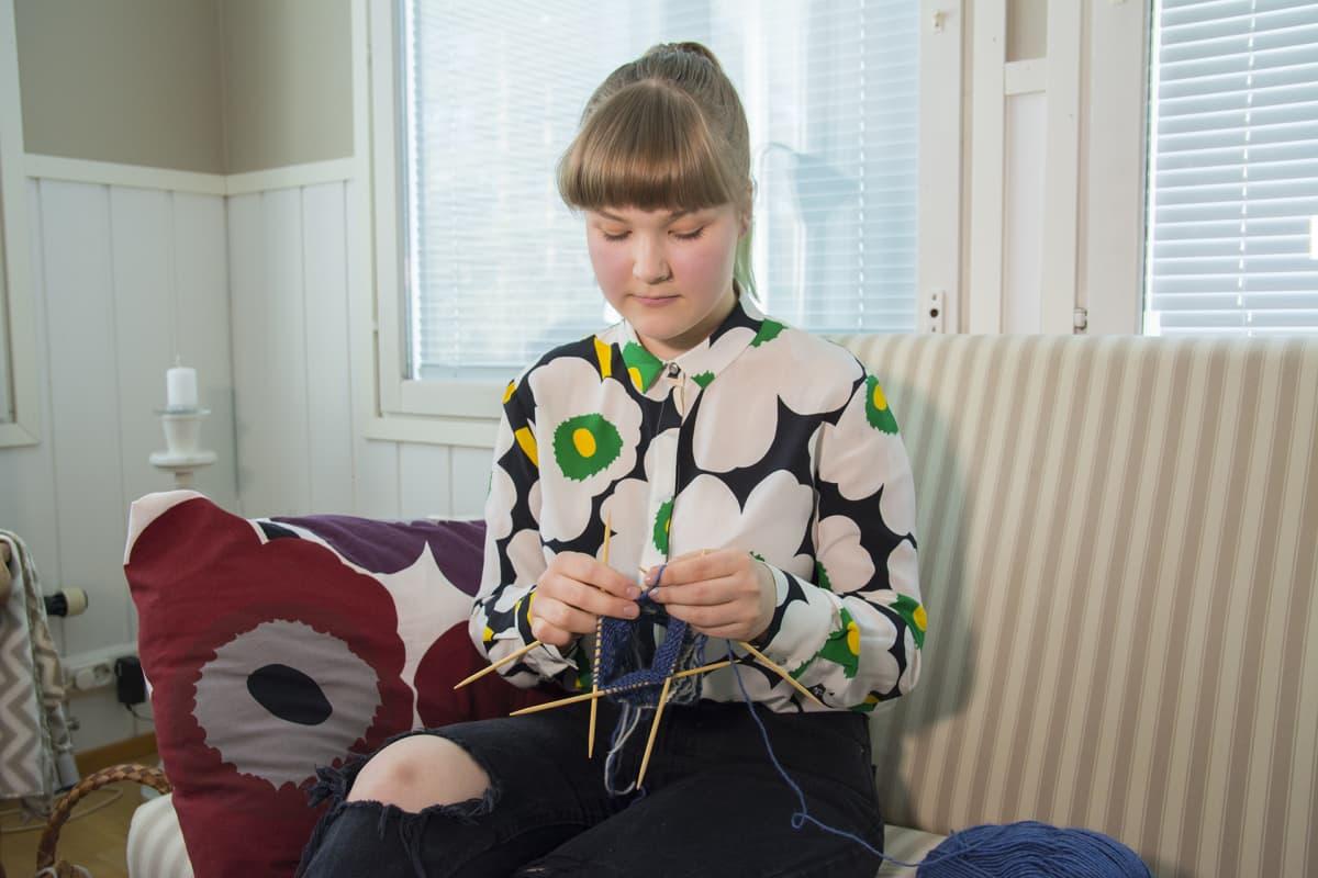 Nuori nainen istuu sohvalla ja neuloo sukkaa.