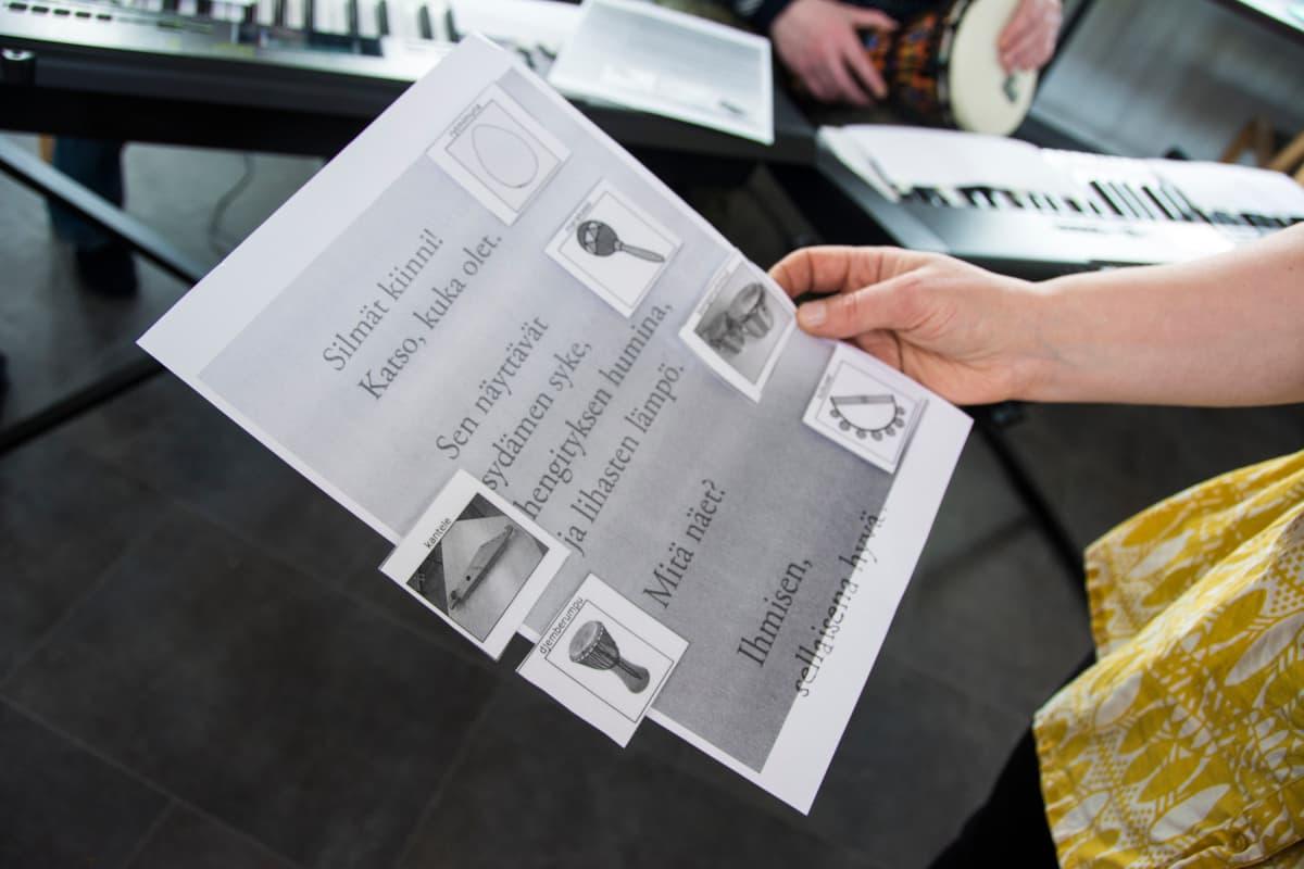 Yhteisömusiikin opettaja pitelee käsissään runoa, johon on kiinnitetty kuvia erilaisista soittimista.