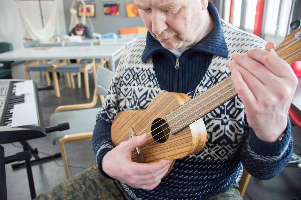 Heimo Suvanto soittaa ukulelea keskittyneenä.