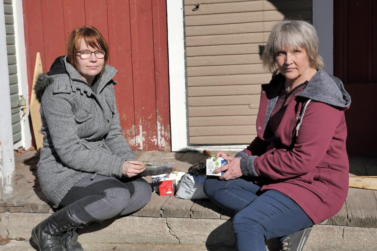Emmi ja Anneli istuvat piharakennuksen portailla
