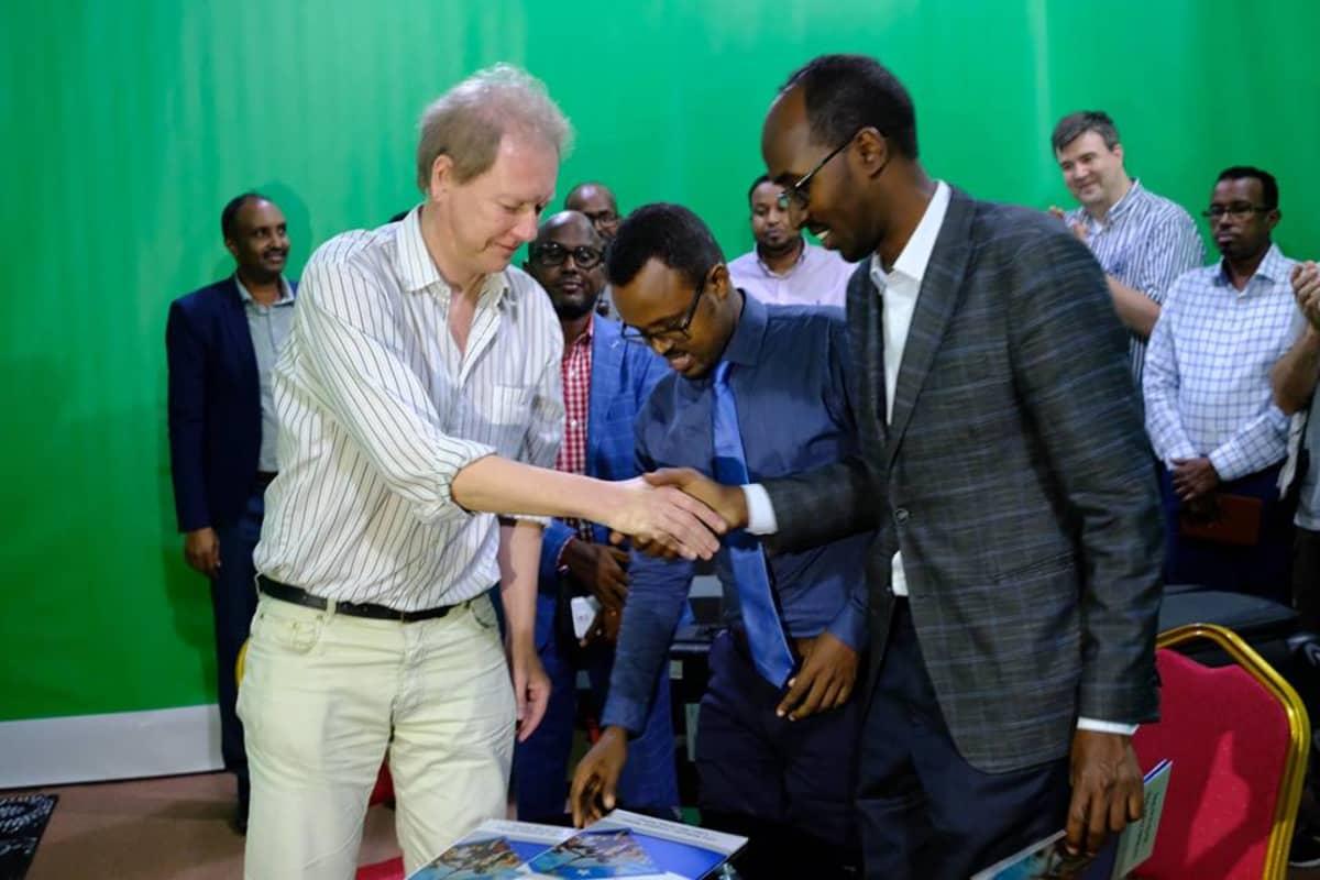 Vikesin koordinaattori Peik Johansson, Somalian viestintäministeriön kansliapäällikkö Abdirahman Yusuf al-Adala ja Somalian kansallistelevision johtaja Liban Abdi Ali virallisissa tunnelmissa.