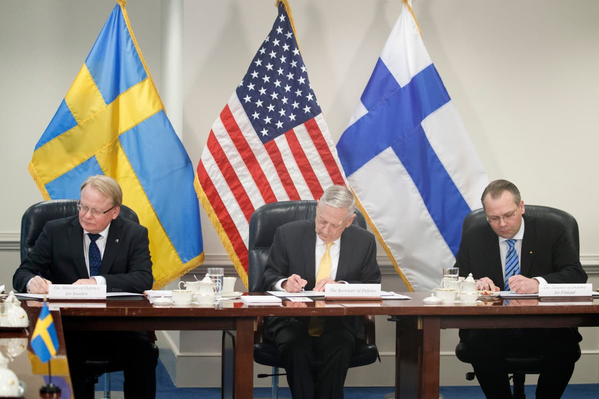 Kolmikko allekirjoittaa pöydän ääressä. Taustalla maiden liput.