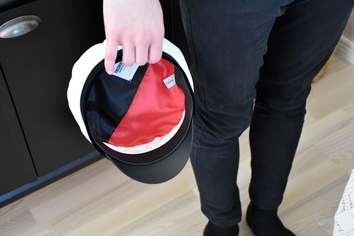 Ylioppilaslakki, jonka sisus on punamusta.