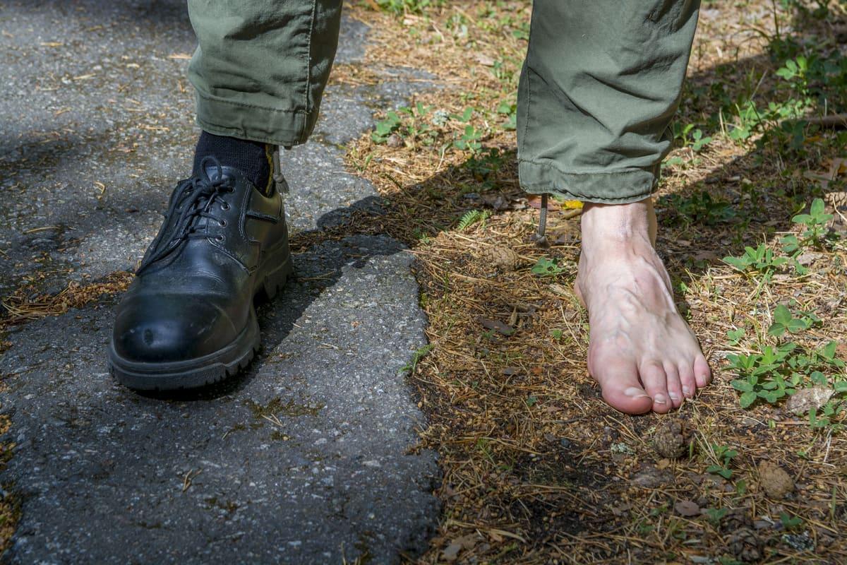 Miehen jalat, toinen asvaltilla kenkä jalassa ja toinen maan päällä avojaloin