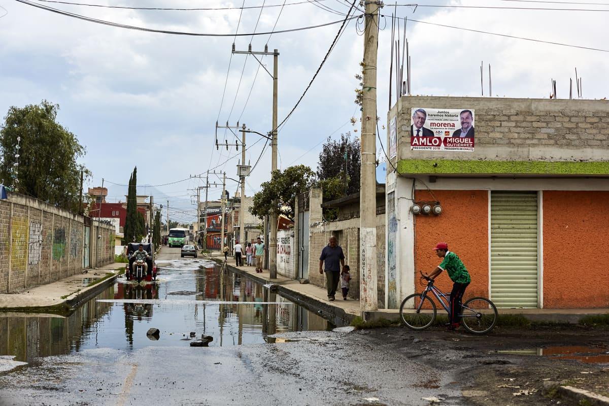 Jätevesi löyhkää kadulla San Juan Tezompan kylässä. Alueella ei ole kunnallista viemäröintiä. Kylässä lähes jokaisen talon seinällä roikkuu Andrés Manuel López Obradorin kannatuksesta kertova mainos.