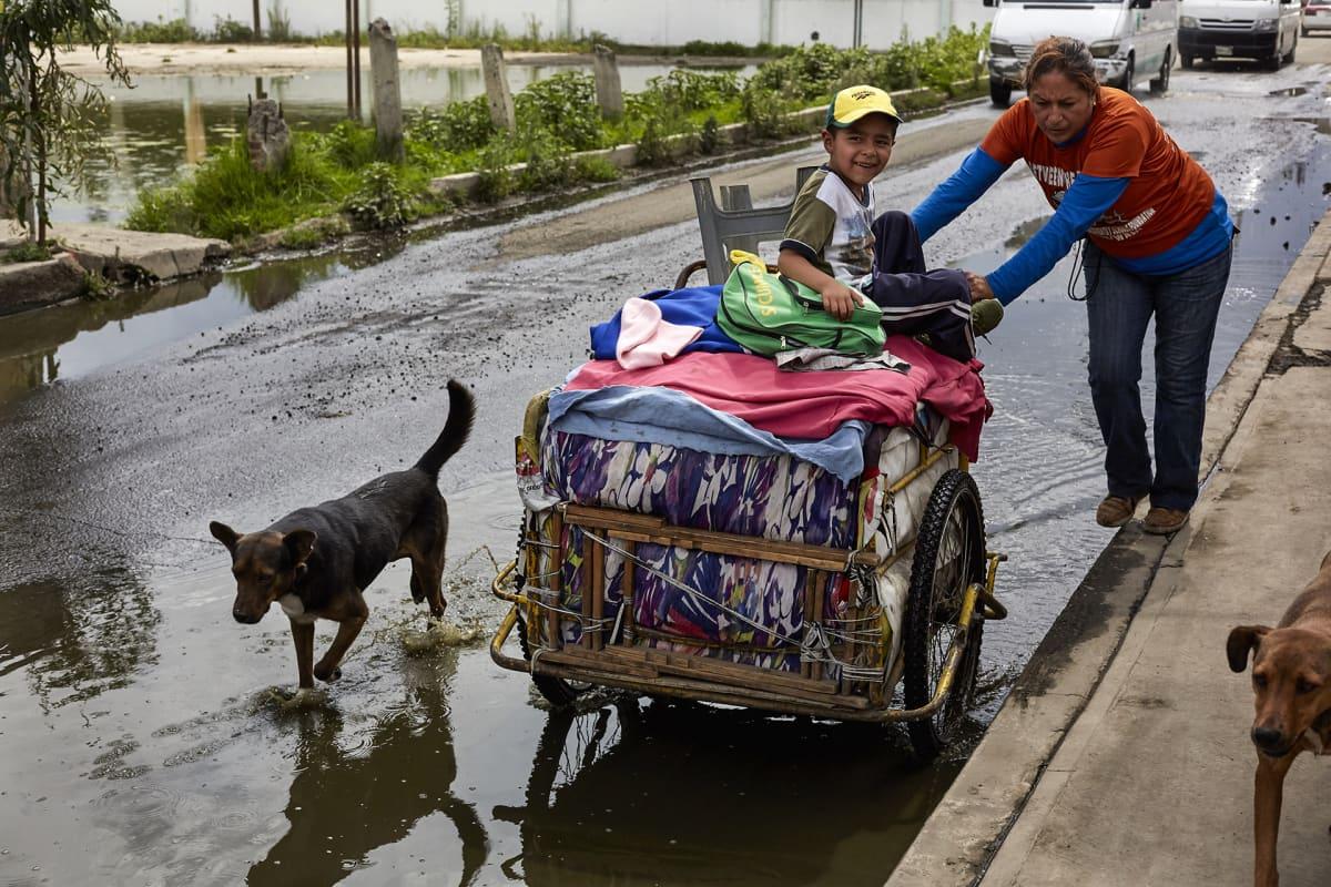 Nainen työntää tavaroitaan löyhkäävän jäteveden halki Chalcon työläisalueella. Alueella ei ole viemäröintiä vaan asukkailla on omat likakaivot.