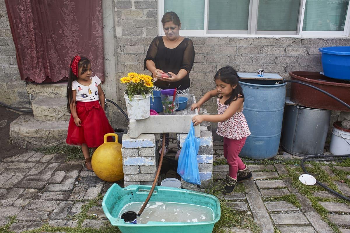 Vettä tulee San Juan Tezompan kylässä vesijohdosta vain parin tunnin ajan lauantaisin, jolloin asukkaat varastoivat sitä tynnyreihin koko viikoksi peseytymistä, tiskaamista, vaatteiden pesemistä ja vessan vetämistä varten. Marisol Vázques Ramos tiskaa astiat ulkona, sillä sisälle vettä ei tule.