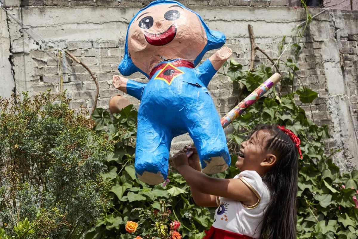 Tyttö lyö karkilla täytettyä piñata-nukkea lastenjuhlissa Chalcossa.
